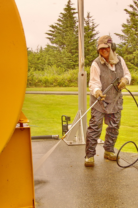 "Caroline Woodward pressure-washing the fuel tanks at Estevan Lightstation during a summer relief stint. ""Ear protectors and full-on sun protection plus steel-toed gumboots are her constant accessories,"" she says, ""a far cry from worrying about whether I should be getting blonde streaks or red highlights in my hair for my book presentations!"""