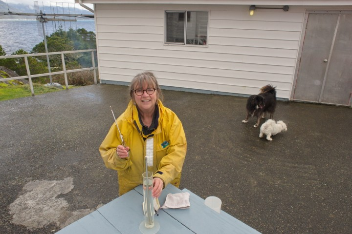 Caroline Woodward measures the sea water temperature and salinity at Nootka Lightstation, a daily task conducted at high tide at selected stations on the BC coast