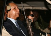 """(FILES) Former Haitian dictator Jean-Claude """"Baby Doc"""" Duvalier and his partner Veronique Roy (C) are protected by armed guards in his limousine after making a surprise return to Haiti in this January 16, 2011, file photo, in Port-au-Prince. Duvalier, who ruled the impoverished Caribbean nation from 1971 until his ouster in 1986, died on October 4, 2014, of a heart attack, officials said. The death of Duvalier, who returned to Haiti in 2011 after 25 years of exile, was announced by the nation's health minister, Florence Guillaume Duperval.           AFP PHOTO / Hector RETAMAL/FILES"""