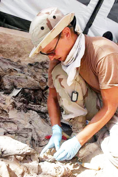 Before Debra Komar became a best-selling author, she spent the last 12 years of her 20-year career as a forensic anthropologist excavating and investigating grisly sites, such as this one in Iraq.