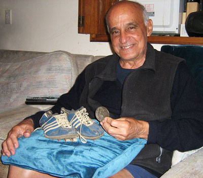 Mike Agostini in August 2010 at Sydney, Australia, with his gold medal and the spikes worn at the Vancouver Commonwealth Games, 1954. Glinda Sutherland photo.